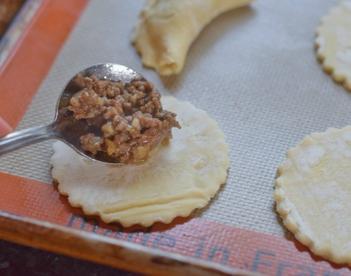 Add a bare teaspoon just off center of your empanada round