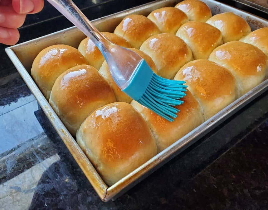 Brushing butter on just baked yeast rolls