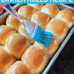 Brushing butter onto a tray of rolls