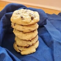Stack of sourdough chocolate chip cookies sitting on a blue cloth.