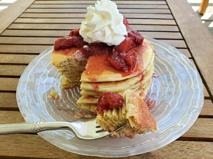 Plate of sourdough pancakes with strawberry syrup and whipped cream